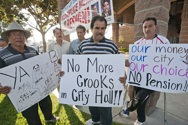 Residents of the predominantly Latino town carry signs urging the firing of the four out of five city council members being paid $96,000 yearly for part-time duties.