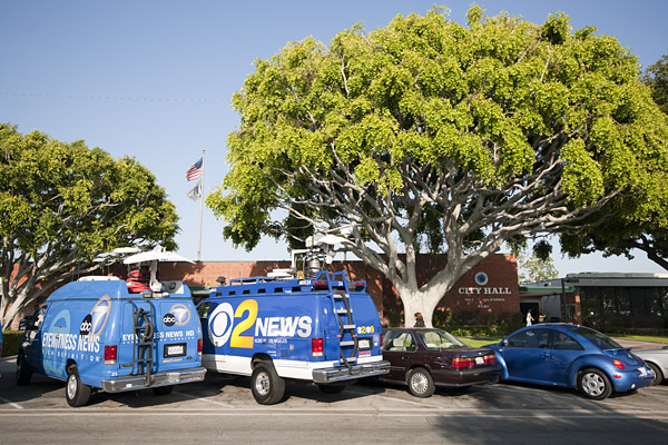 News vans line up outside Bell City Hall, Monday, July 26, 2010, as residents of the working class city in Los Angeles County demand the ouster of city officials whose high salaries were revealed a week earlier by the Los Angeles Times.