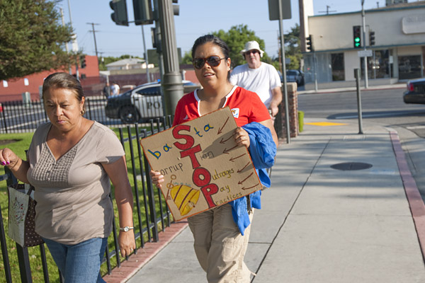 A Bell resident carries a homemade sign with messages in English and Spanish that decry corruption in their city government.