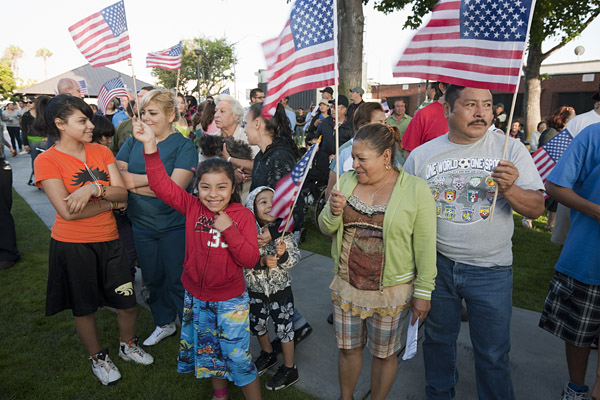 A family waves flags to show their patriotism as they wait outside the city council meeting.