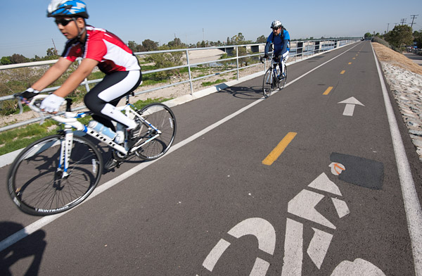 Cyclists ride the Lario Trail along the Los Angeles River near Willow Street in Long Beach.
