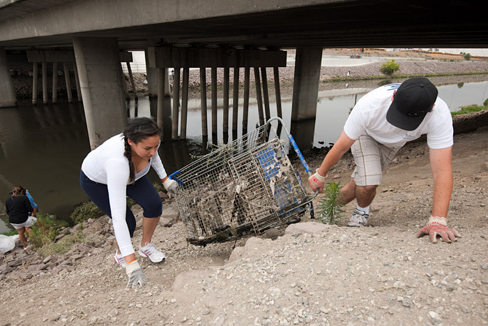 Volunteers drag a shopping cart out of the stream and up the bank.