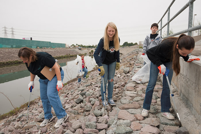 Members of a local dance troupe help gather debris along the rock and concrete lined stream.