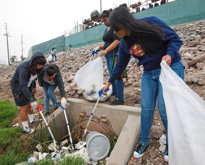 Four volunteers remove styrofoam and other waste from a drain on the bank of the stream.