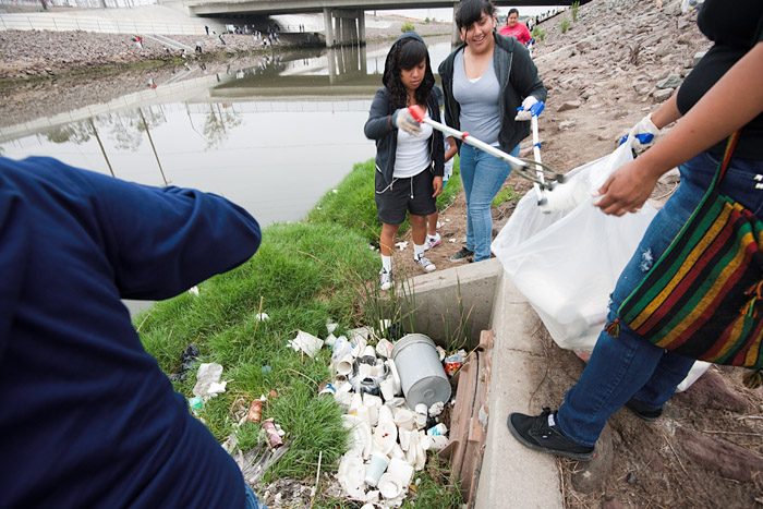 Four volunteers remove styrofoam and other waste from a drain on the bank of the stream. Most of the student volunteers are black or latino.