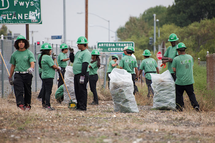 Members of the L.A. Conservation Corp clear brush and debris from a patch of land near Vermont Avenue and Artesia Boulevard.