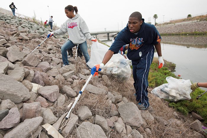 Serra High School students remove trash from the bank of the channel.