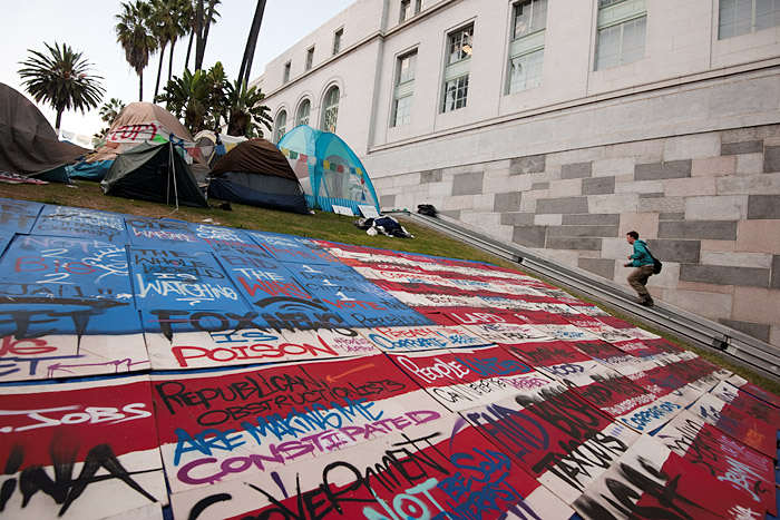Populist slogans cover an American flag graphic on the lawn outside City Hall.
