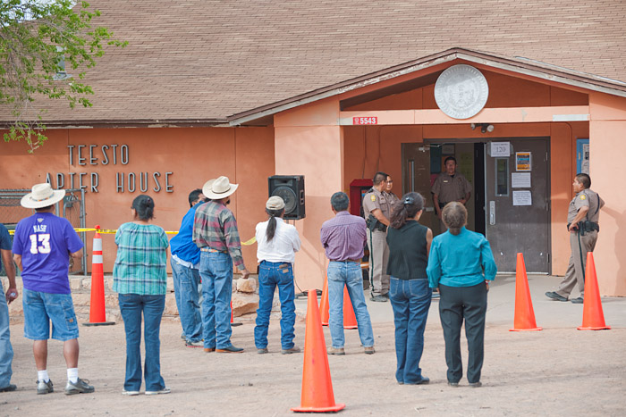 Navajo people concerned about giving up their water rights listen through a loudspeaker outside the chapter house. Despite empty seats inside, tribal police closed the doors to the meeting citing crowded conditions.