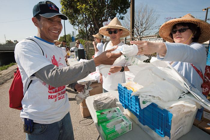 A volunteer receives gloves and plastic bags.