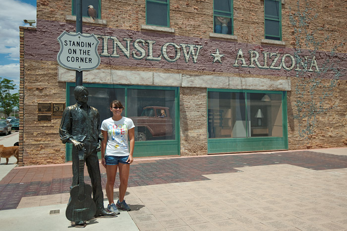 A girl poses with a statue of a musician placed at the intersection of Second Street and Kinsley Avenue in Winslow, Arizona, in reference to the Eagles' hit song, 'Take it Easy,' written by Jackson Browne and Glenn Frye.