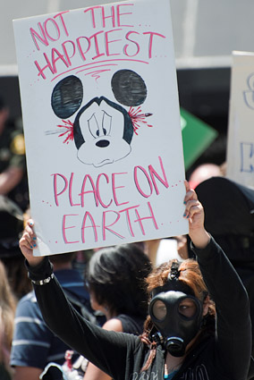A protestor's sign alludes to the Disneyland motto in deprecating Anaheim as