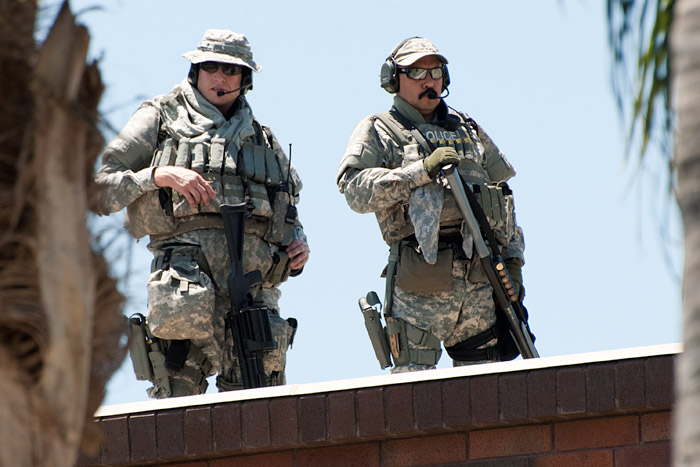 Police snipers dressed in military fatigues survey the demonstration from the rooftop of the Anaheim Police Department and surrounding buildings.