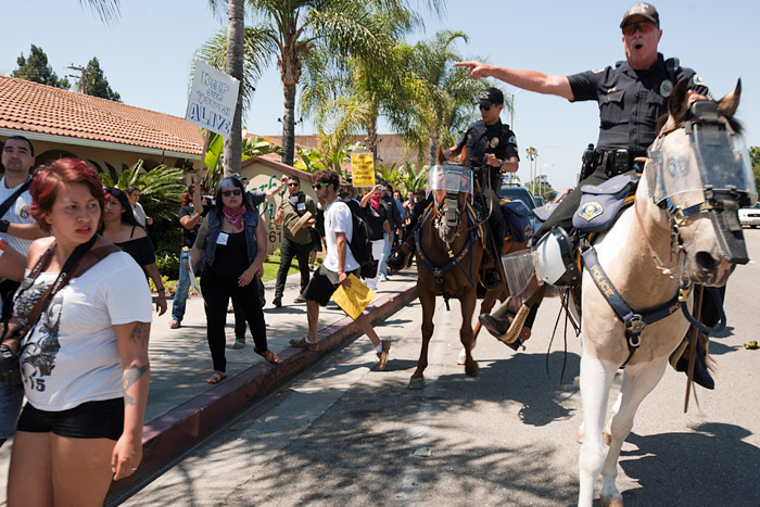 A sergeant with the Anaheim Police Mounted Unit temporarily drives protestors off the street.