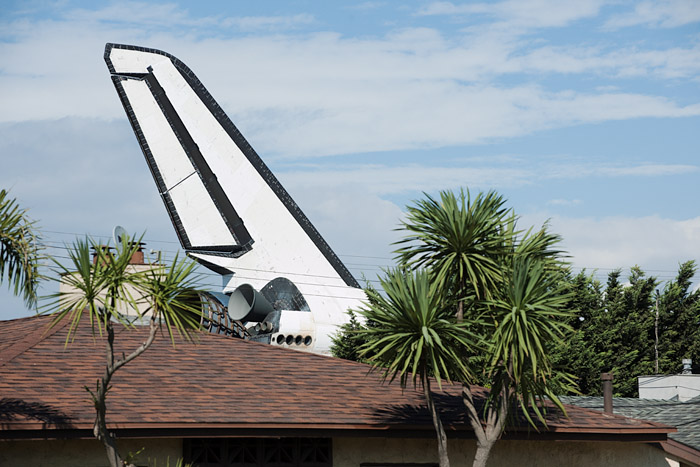 The shuttle's fin protrudes shark-like above residential roofs in Westchester.