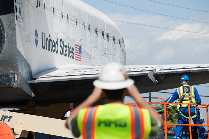 Workers monitor the shuttle as it approaches a 45 degree right turn onto Manchester Avenue.