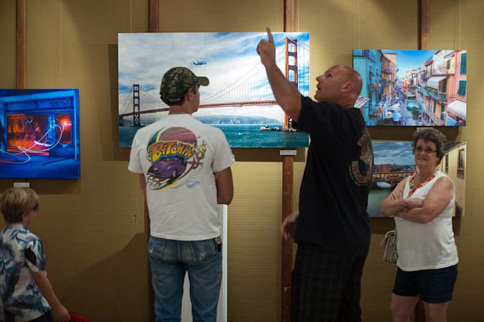 Art enthusiasts discuss works displayed by local painters at the art show.