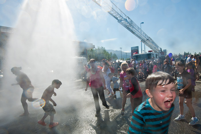 An Anchorage Fire Department hose saturates revelers Saturday, July 13, 2013, during the Bear Paw Festival at the Eagle River district of Anchorage, Alaska.