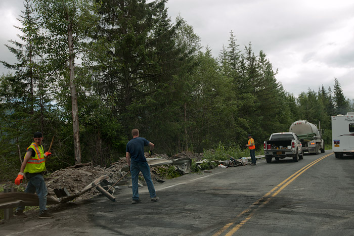 A construction crew clears the road after a tanker trunk overturned on the Seward Highway near Moose Pass, Alaska. The sole land route connecting the eastern Kenai Peninsula with Anchorage was blocked for around an hour.