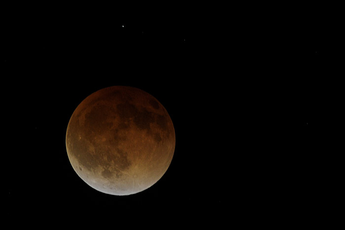 The moon appears reddish-amber as it passes behind the earth's shadow during a total lunar eclipse.