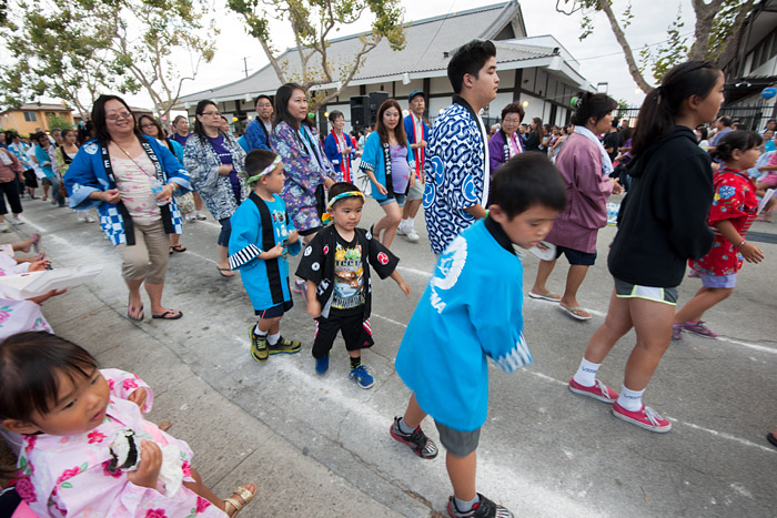 Bon odori dancers line Halldale Avenue in Gardena, California, on Sunday, August 3, 2014, as part of the annual Obon Festival at the Gardena Buddhist Church.