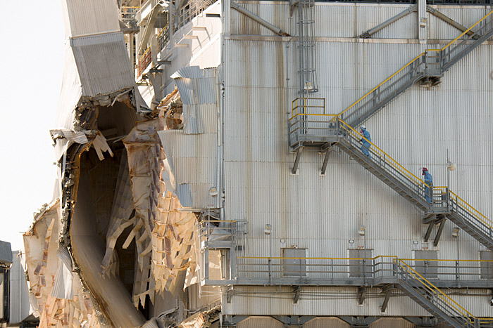 Workers ascend an exterior staircase of the damaged refinery in Torrance, California, on Tuesday, March 3, 2015.