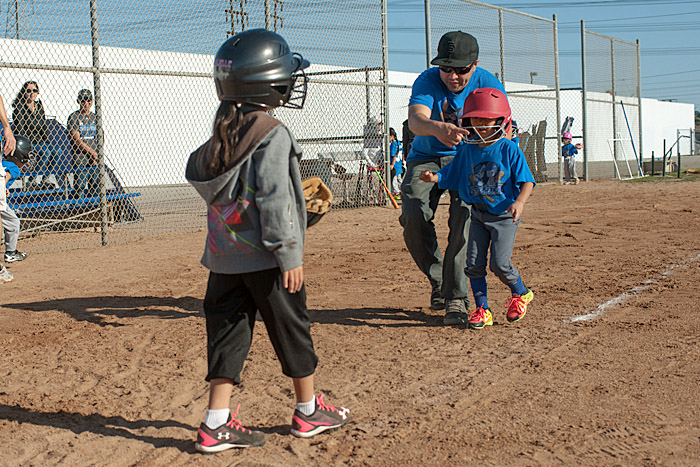 Coach Jeff shows Noe a path around the catcher during the first inning.