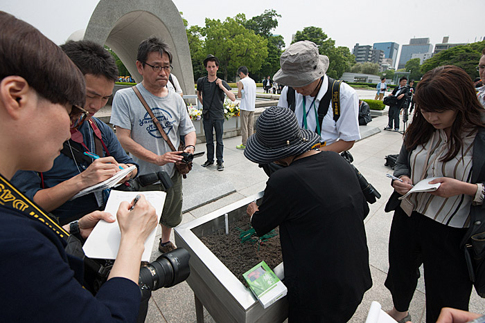 Reporters listen diligently and take notes as a hibakusha, a-bomb survivor, speaks while lighting incense at Peace Park.