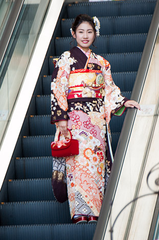 A woman in kimono descends an escalator near Sogo Department Store.